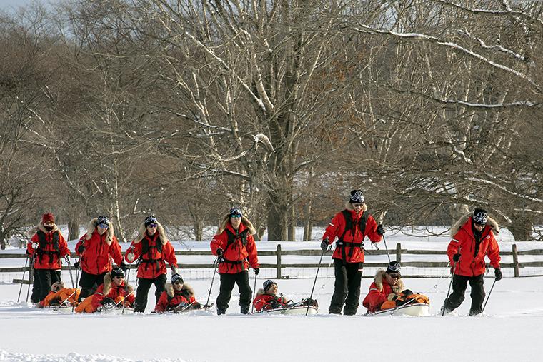 北海道の牧場を借りて合宿を行った。スキーを履き、荷物を載せたソリを引いて歩く様子