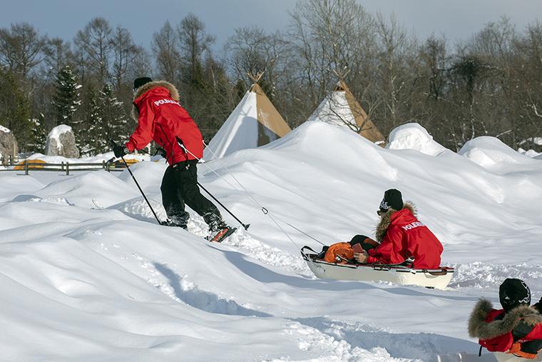 雪が積もる牧草地を使いソリを引いて歩く訓練