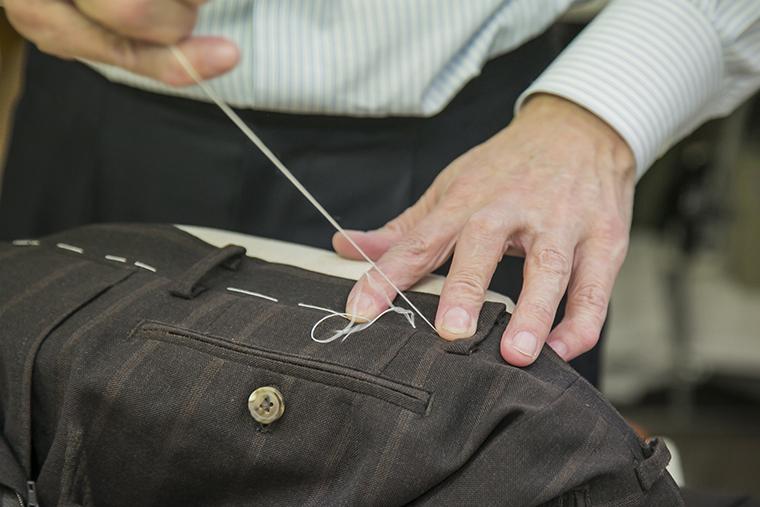 サイズ調整の依頼があったパンツのベルト帯部分を仮縫いする荒関さん