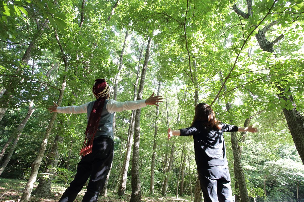 森林の中で両手を広げているスパイシー丸山と名久井