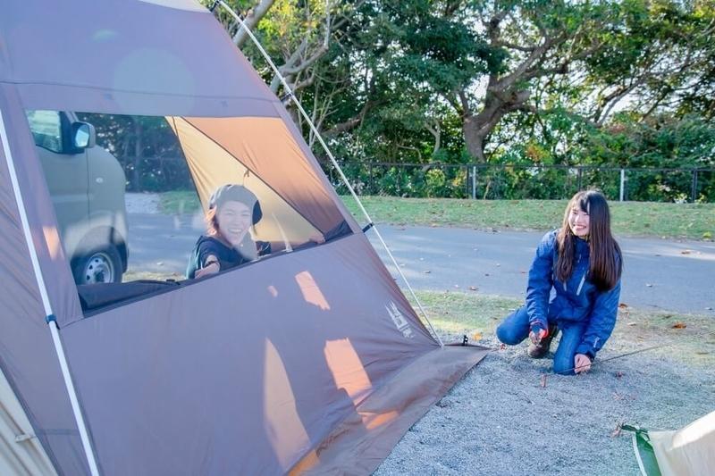 三沢真実さんと茅ヶ崎みなみさんがキャンプサイトで設営を進めている写真