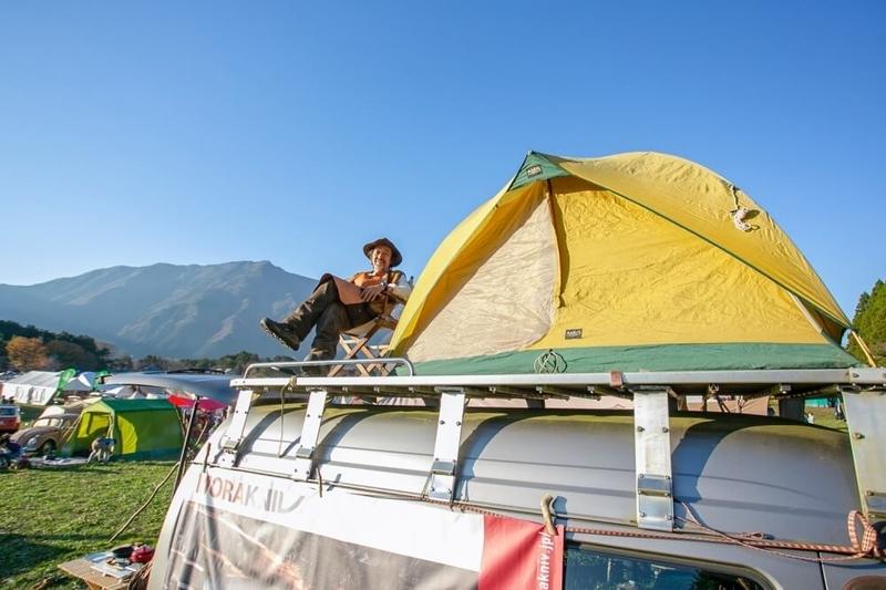 クルマ×アウドドアのイベントLet's chillout! 長野修平さんの日産キャラバンのルーフにテントを設営し、くつろいでいる様子