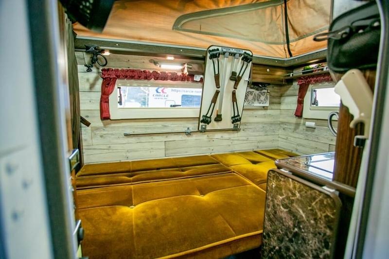 バンライフイベント「VANTERTAINMENT FES vol.0」(バンタメ)。YouTuberのケンキャン(ケンケンさん&やまめさん)の愛車バロッコの車内。ソファーを倒したベッドモード時の様子
