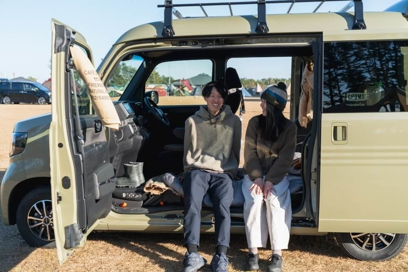 Hondaの軽自動車N-VANのドアを開けて並んで座る野外のもりこさん夫婦