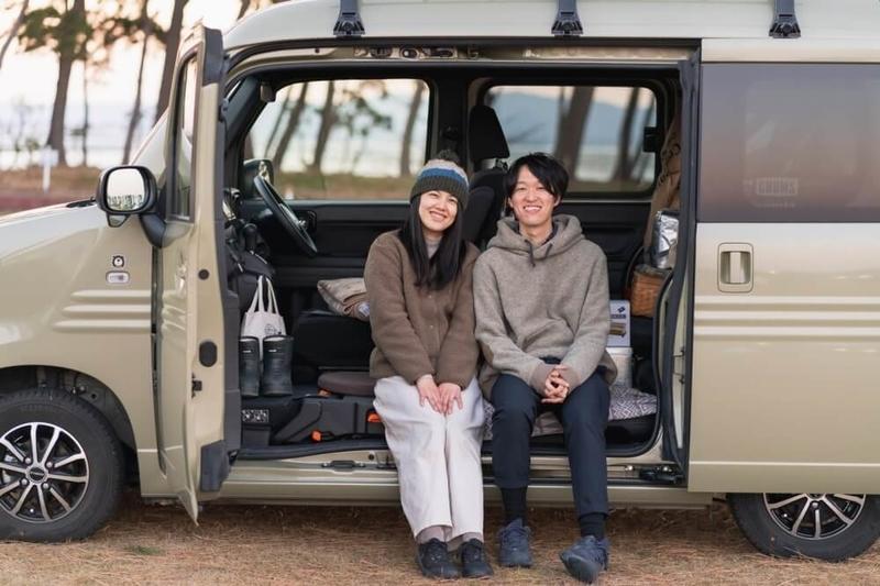 Hondaの軽自動車N-VANのドアを開けて座る野外のもりこさん夫婦