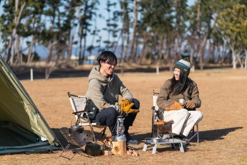 キャンプ場で椅子を並べて話す野外のもりこさん夫婦