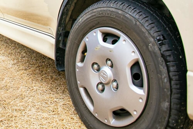 クルマの日常点検・メンテナンス。タイヤのサイドウォールをチェックしている画像