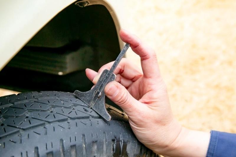 クルマの日常点検・メンテナンス。タイヤの溝の残りを、デプスゲージを使って調べている様子
