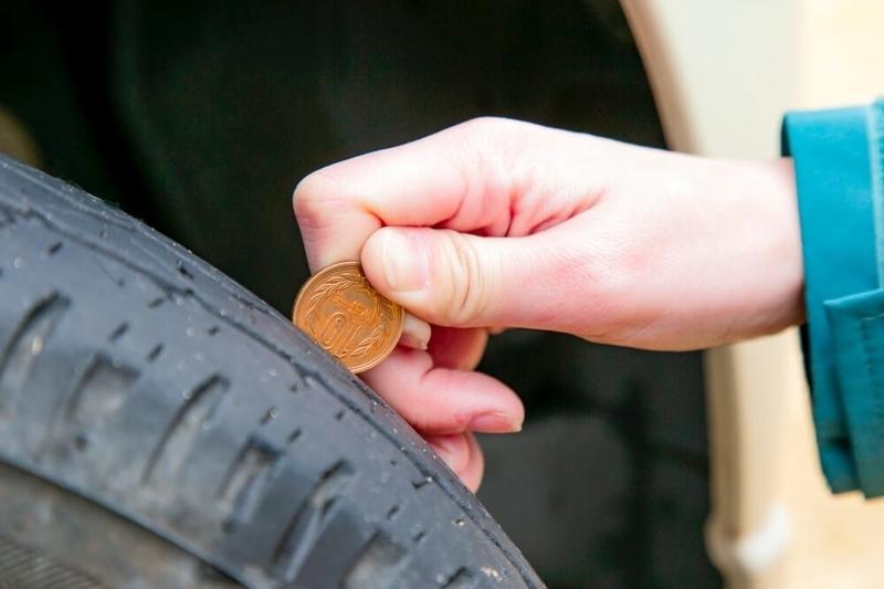 クルマの日常点検・メンテナンス。タイヤの溝の残りを、10円玉を使って調べている様子