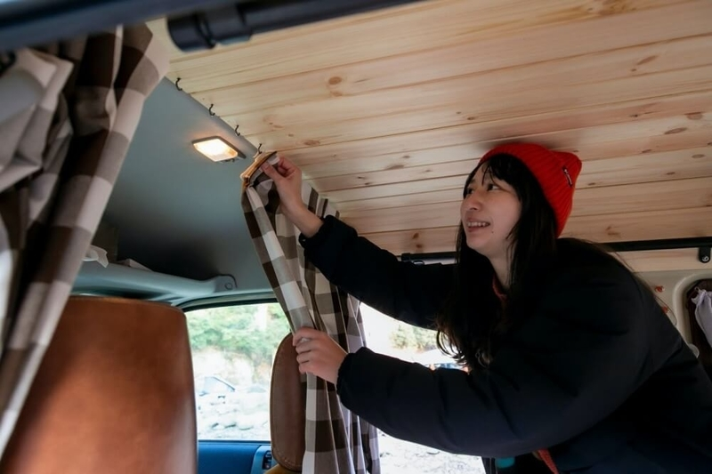 森風美さんが板張りの天井にヨートフックを使いカーテンを取り付けている様子