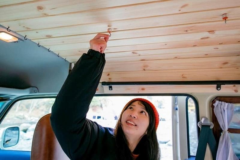 森風美さんが板張りの天井に仕込んだマグネットを説明するため、天井にマグネットフックを取り付けている様子