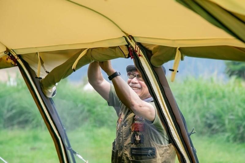 テントのパネルを内側に巻き、水が溜まることを防ぐ様子を説明する福吉さん