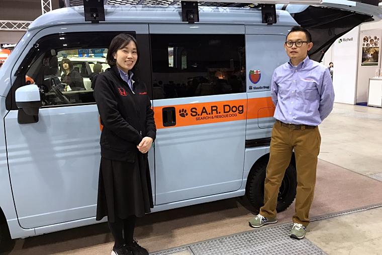 Honda Dogコーナーに展示されている車「S.A.R. Dog Concept」の前に立つホンダアクセス 商品企画部のデザイナーである加藤 智久さん(右)と、企画担当の蓑和(みのわ) 佳苗さん(左)
