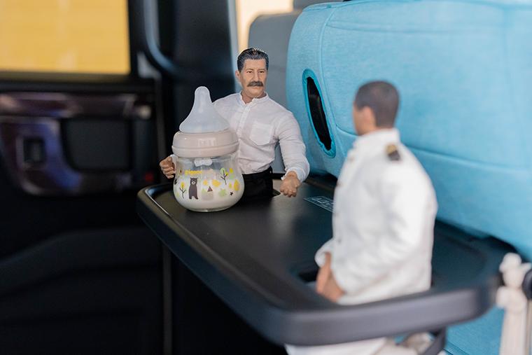 シートバックテーブルに哺乳瓶を置いてみるヨシダさん