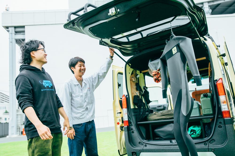 TRIP VANのテールゲートバーにウェットスーツをかけて乾かせることを説明するホンダアクセス商品企画部デザイナーの渡邊岳洋さん