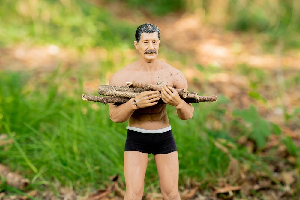 焚き火用の薪を手に持つヨシダさん