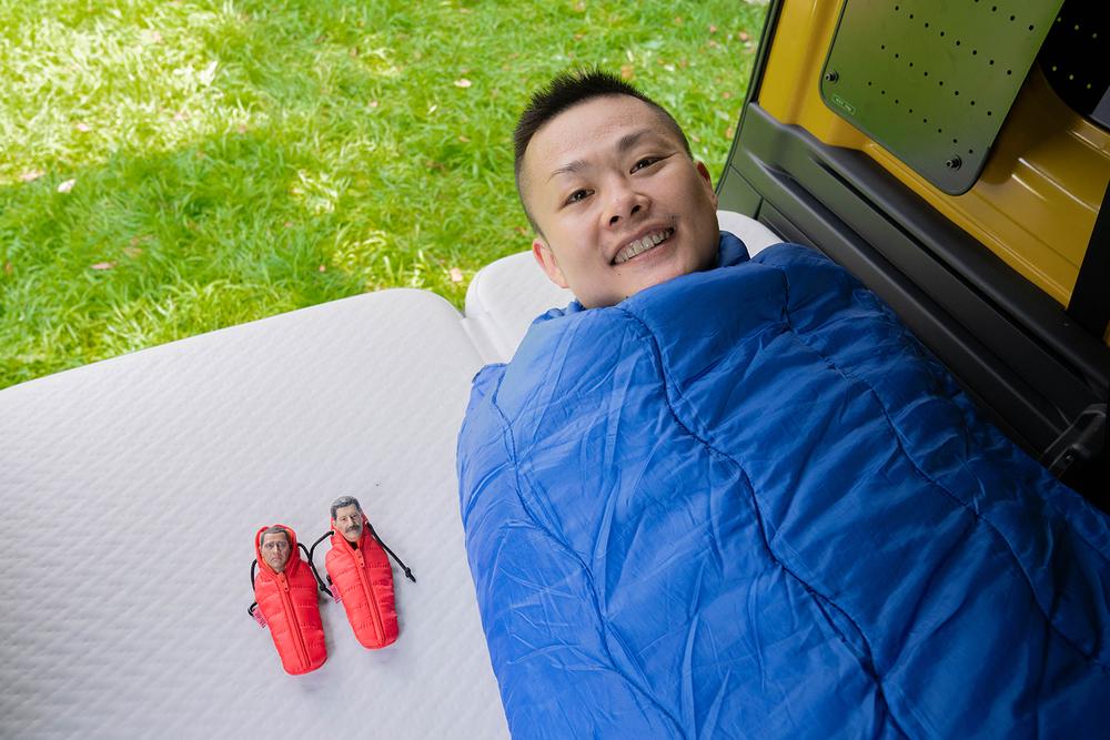 N-VANで、寝袋に入って車中泊するおじさんたち。