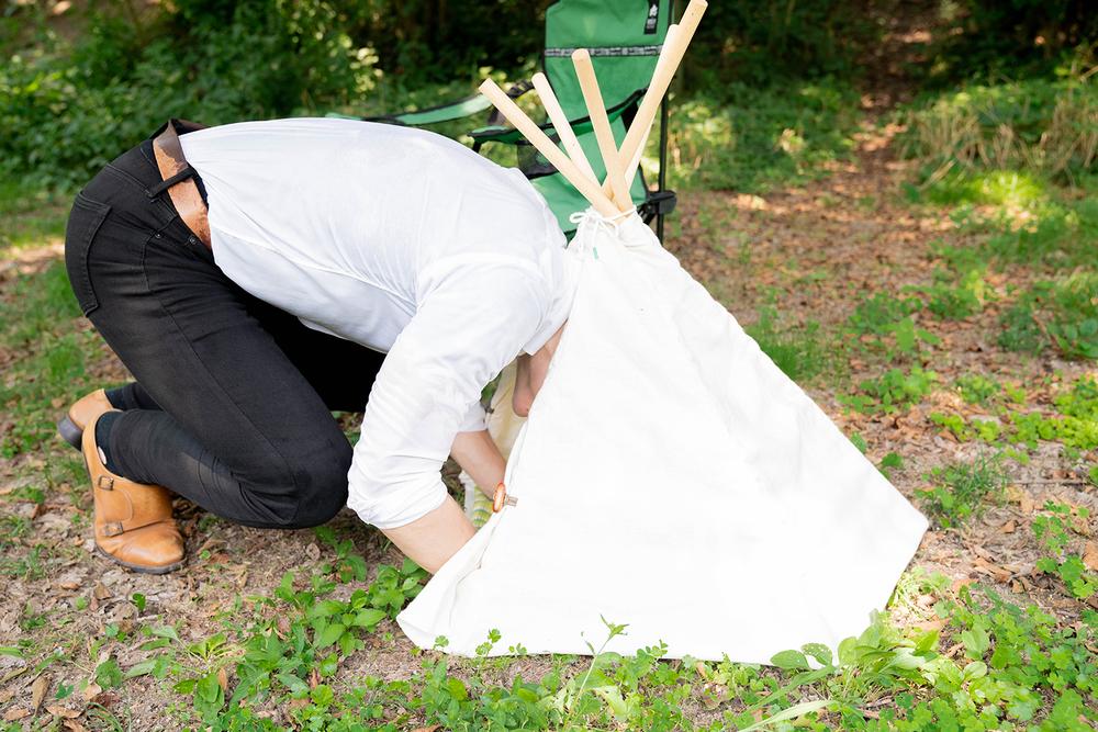ミニサイズのテントに頭だけ入れた横田さん
