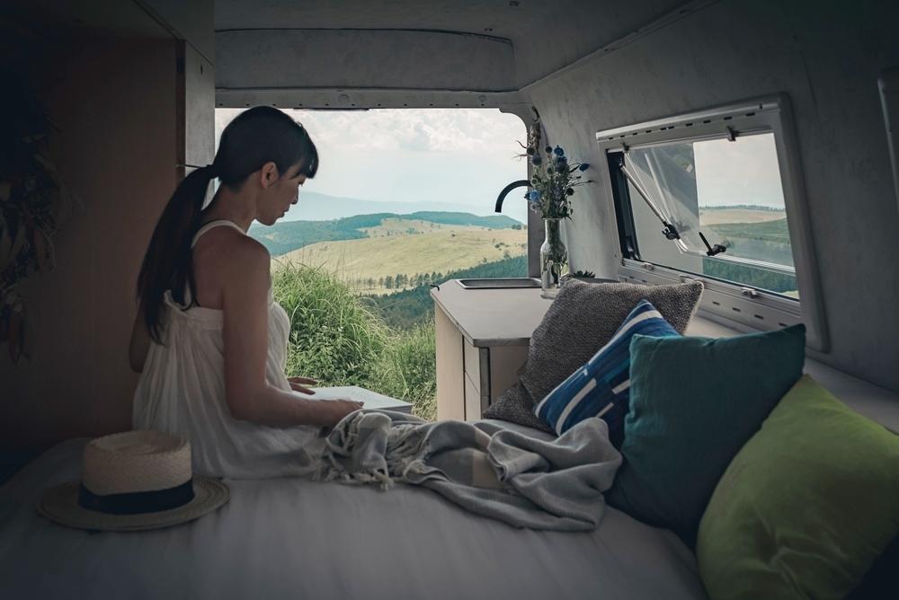 車中泊できるようにカスタムしたベンツの車内で、ベッドに座る奥はる奈さん