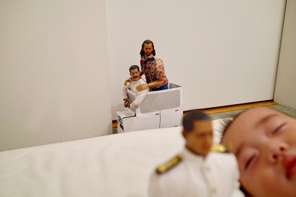 夢からさめたミフネさんの後ろに、クルマに乗ったヨシダさんとニコラスがいる