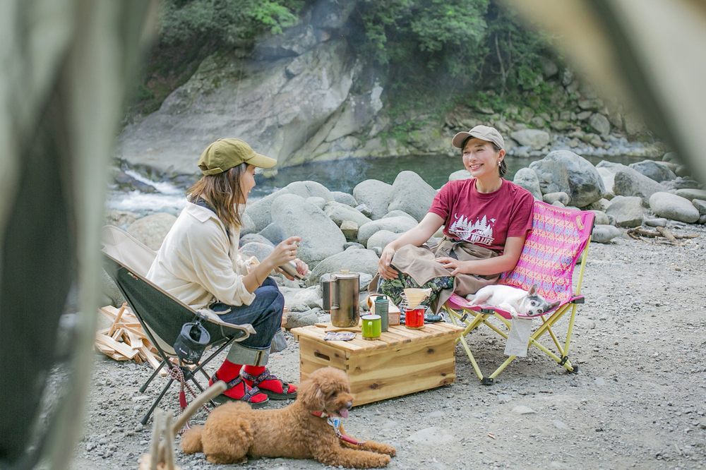 川原でキャンプする芳美リンさんと内舘綾子さん、ペットの犬と一緒に