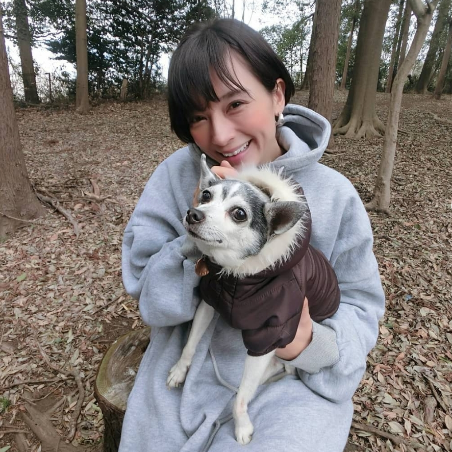 ダウンを着た犬を抱く芳美さん