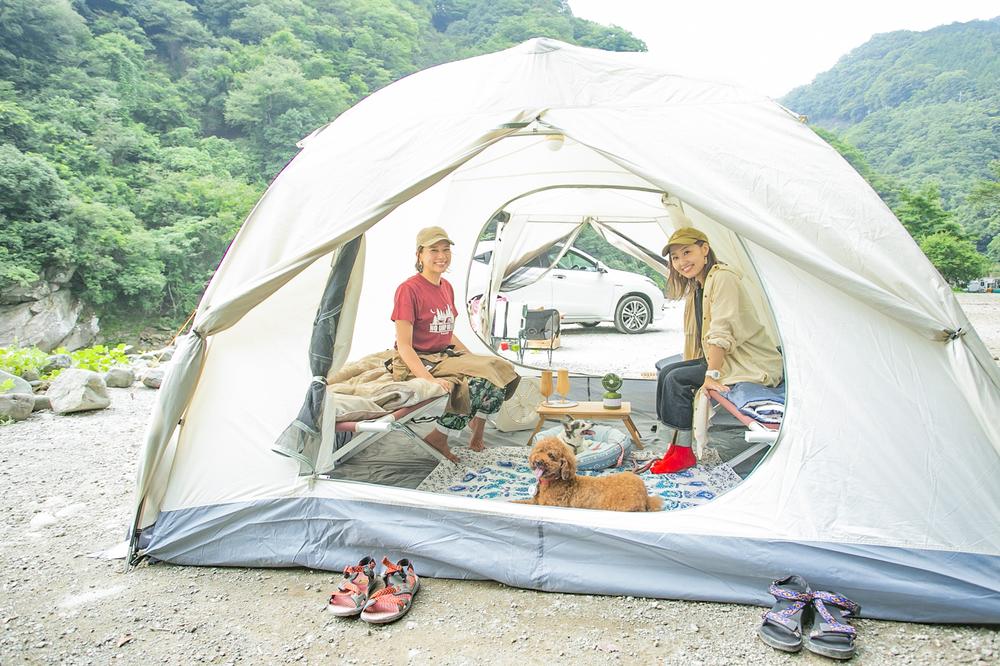 テントの中でくつろぐ女子キャンパーとペット