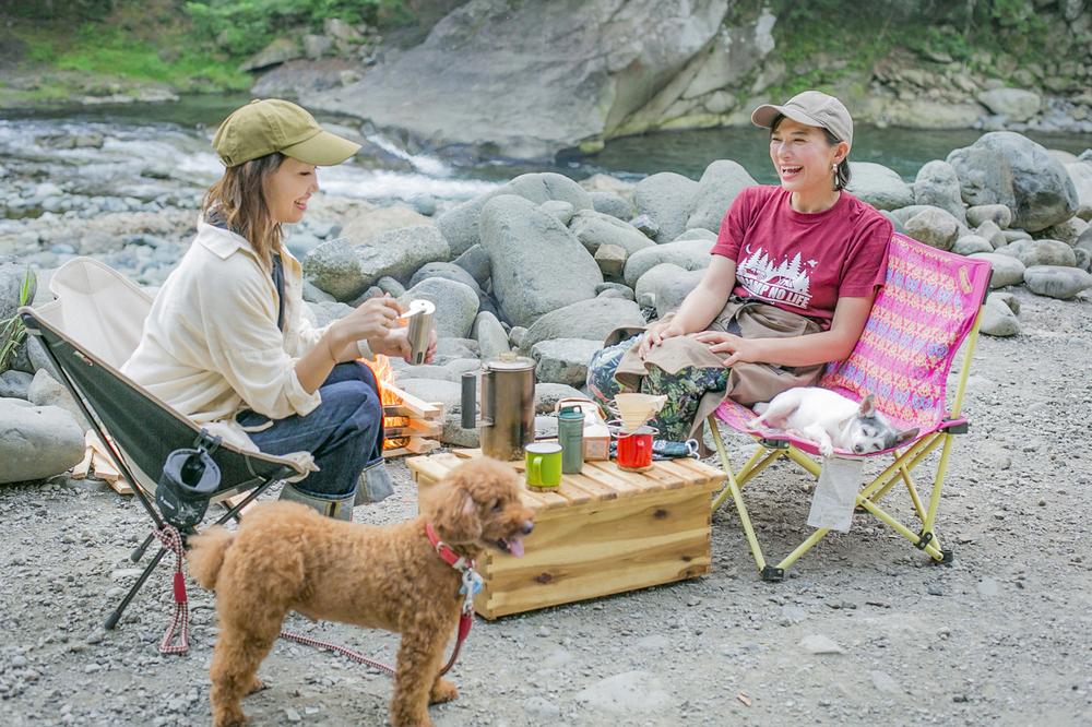 キャンプ場で焚き火をしながらコーヒーを飲む女子キャンパー