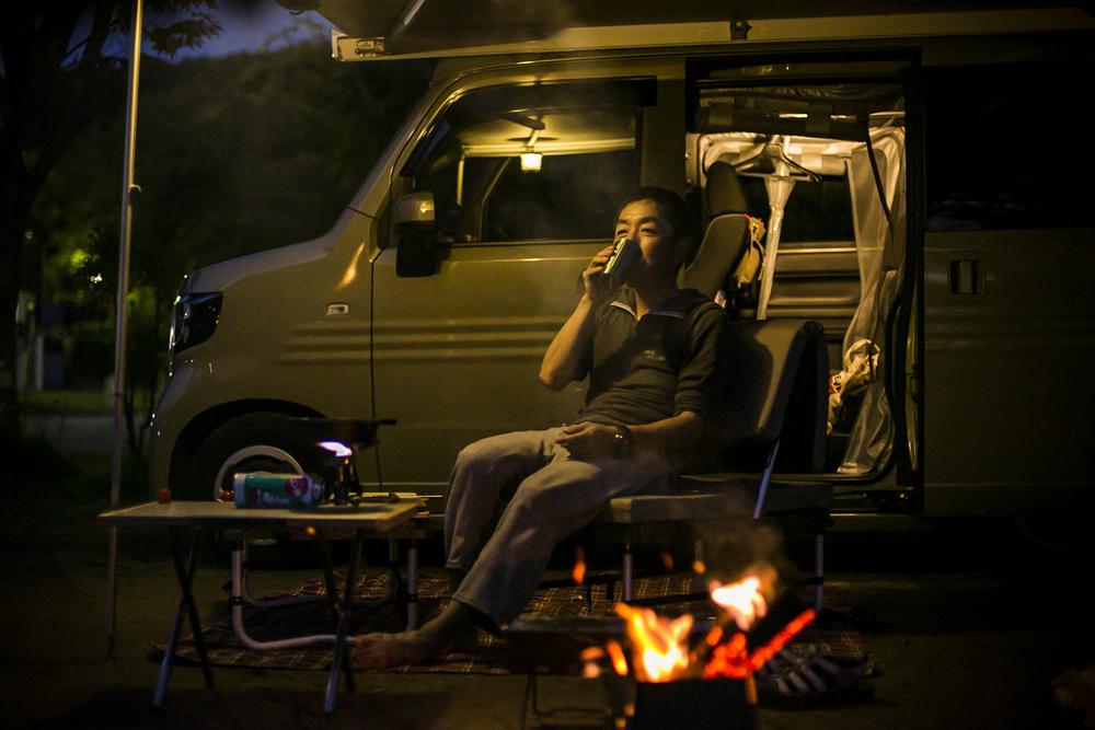 焚き火の前で、キャンプする男性