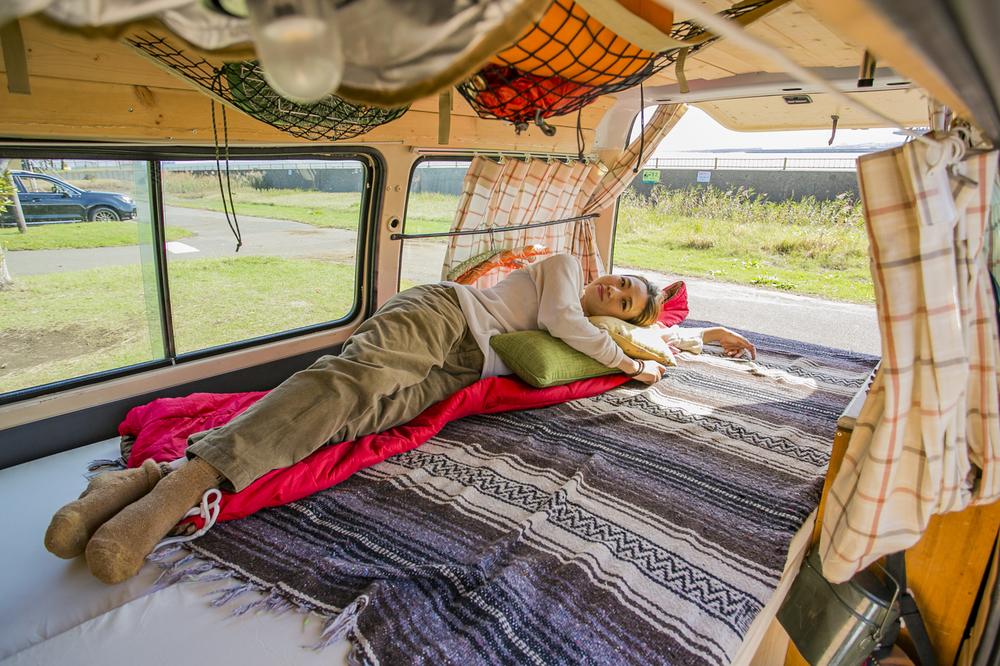 愛車「サンシー号」のベッドに寝そべるYURIEさん
