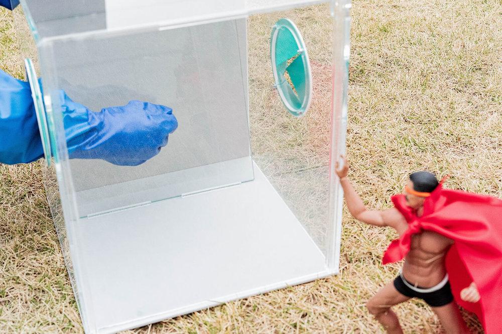 ブルーの手袋をした手がケースの中で、スマートレスキューを使ってガラスを割ろうとしている