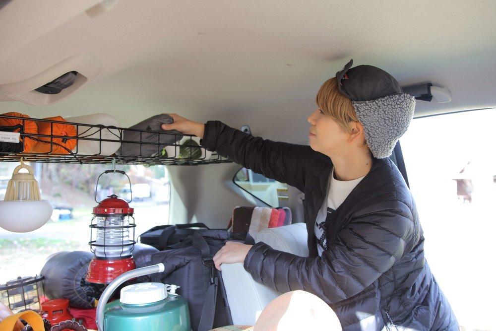 ルーフラックにキャンプ用品収納をする美加さん