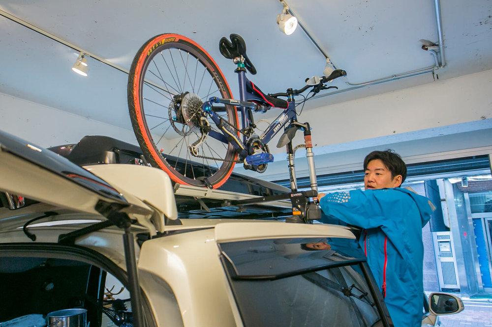 小澤さんがマウンテンバイクの前輪を外して屋根のキャリアベースに固定している