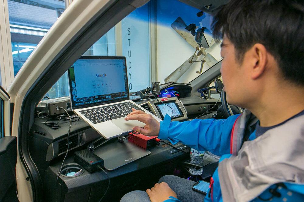 フリードスパイクの助手席でパソコンを操作する男性