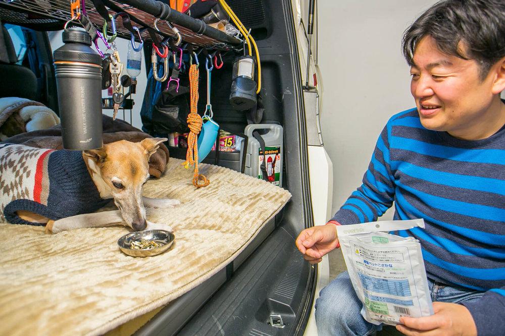 ペットの犬におやつをあげる男性
