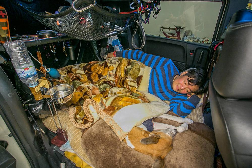フリードの車内でペットの犬と一緒に寝ている男性