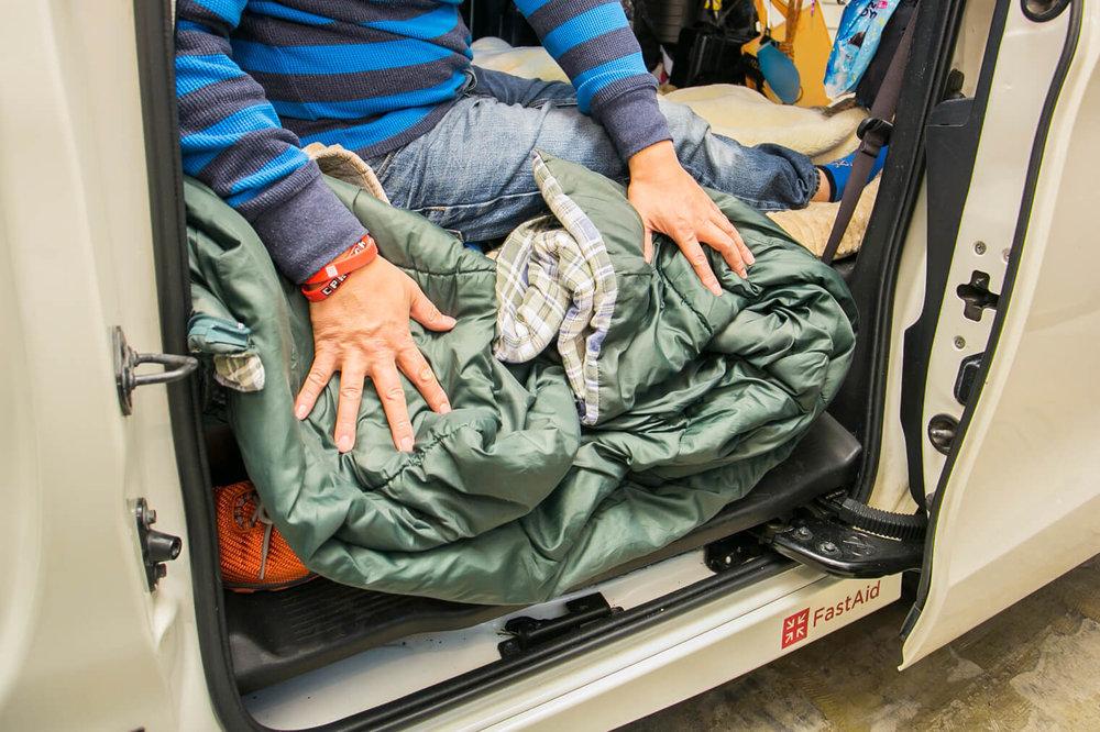 車中泊するとき、ドアとの隙間に余った寝袋を挟むと冷気が入ってこないと語る男性