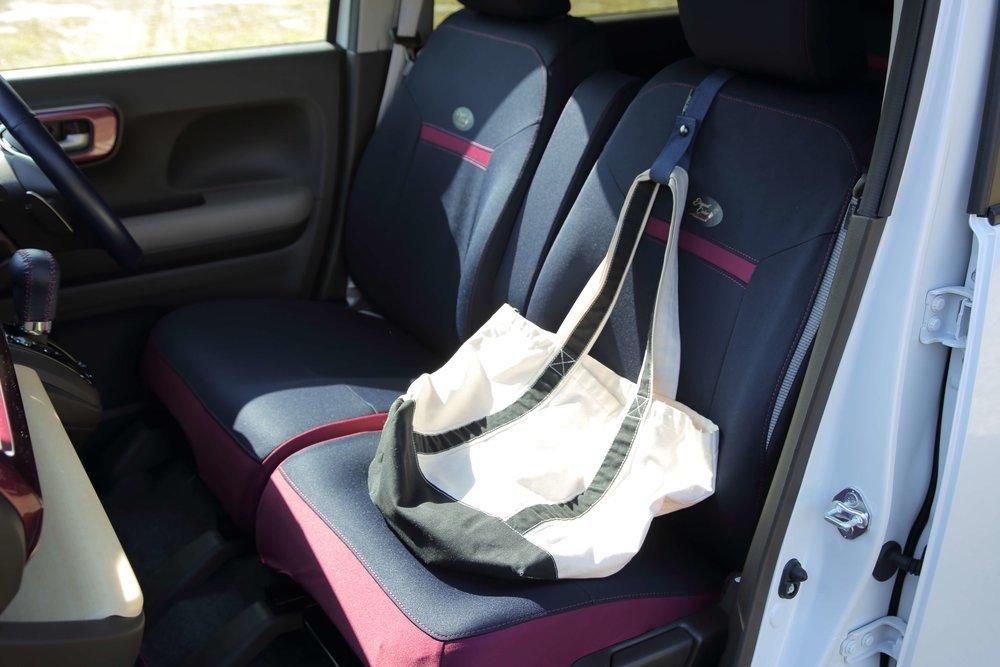 布製のカバンを助手席に置く様子