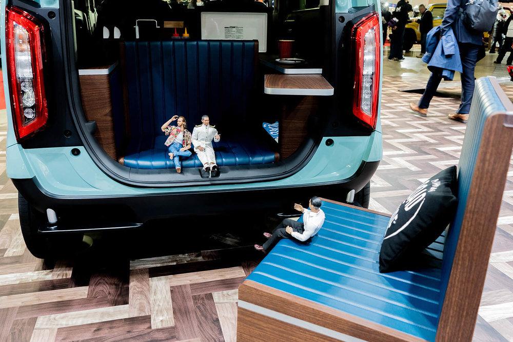 N-WGN ROAD SIDE conceptのリアゲートを開けてソファに座るミフネさんとニコラス。クルマから出した可動式のソファに座るヨシダさん