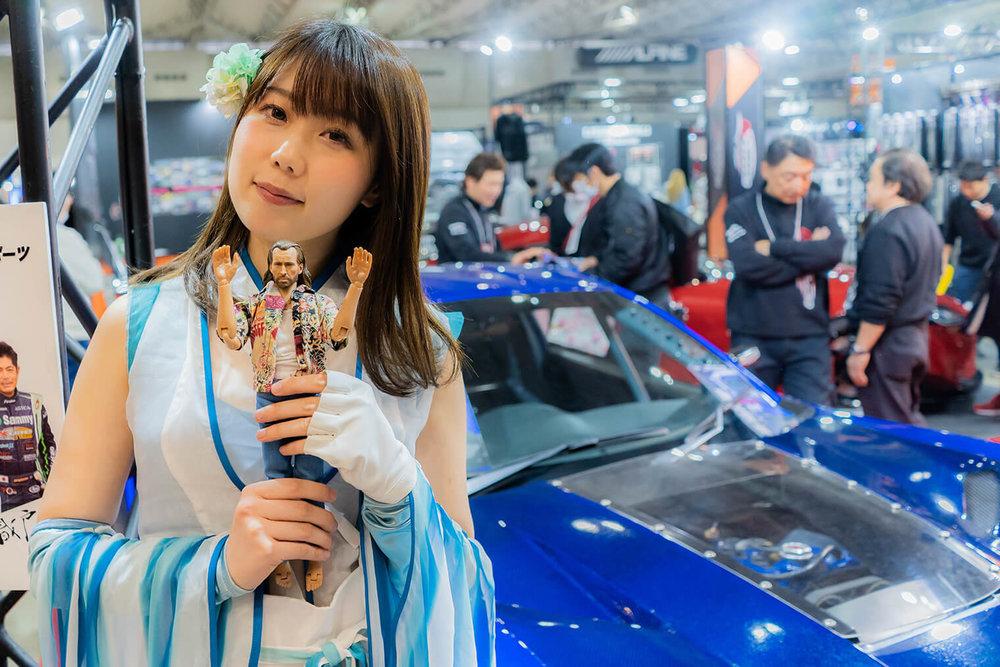東京オートサロンのブースにいる美しいコンパニオンが手にニコラスを持っている