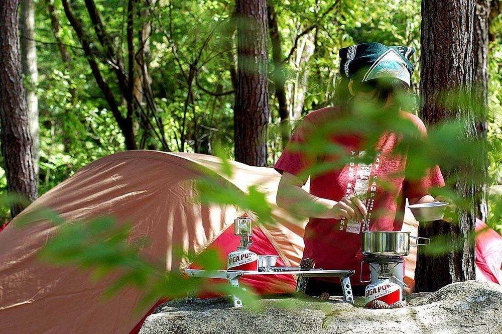 車中泊のプロがおすすめ便利グッズ、車中泊の必需品、装備と道具を紹介。オートキャンプ場で、食事を作る女性