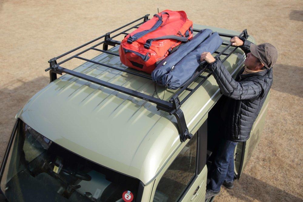 ルーフキャリアにキャンプ用品を積載する様子