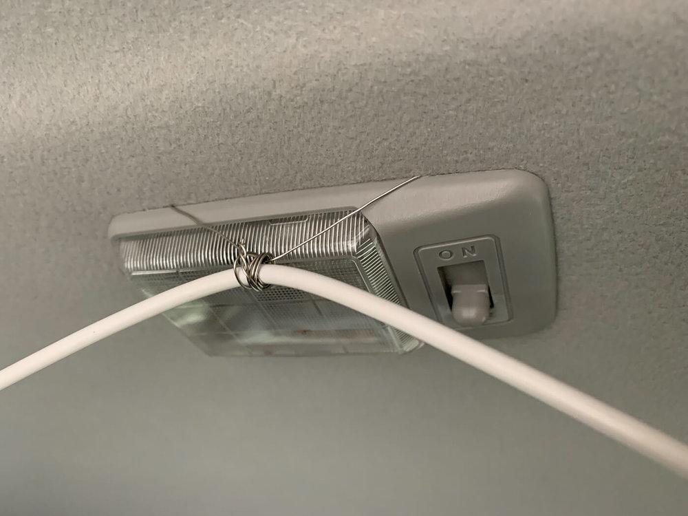 車内灯に針金でカーテンワイヤーを設置する様子