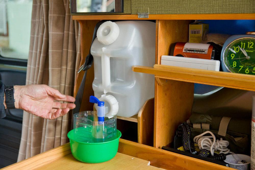 N-VAN内の棚に設置した飲料水タンクから水を出している