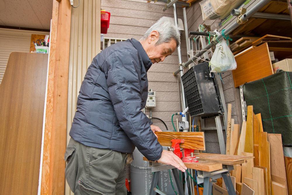 作業小屋で板を加工する男性