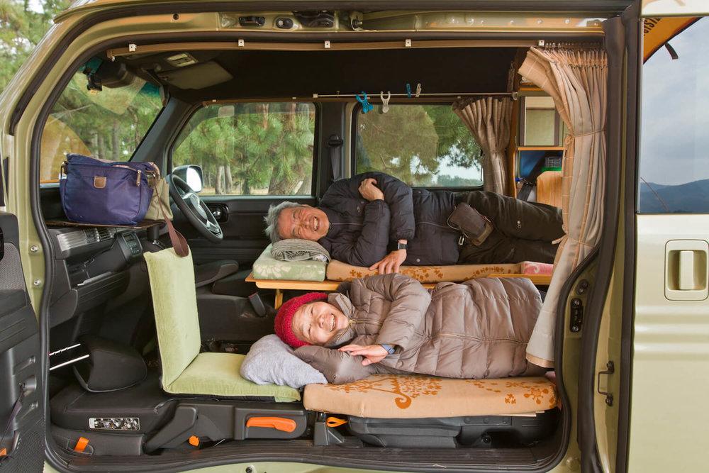 N-VAN内のベッドに横になって、にっこり笑顔のご夫婦
