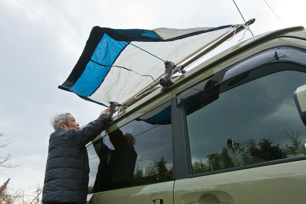 ルーフに設置した物干し竿に、雨よけシートを紐でくくりつける男性