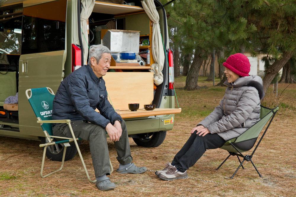 テールゲートキッチンの前で椅子に座って談笑する夫婦