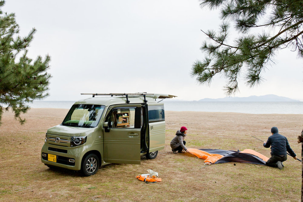 キャンプ場で、カーサイドタープを組み立てる夫婦