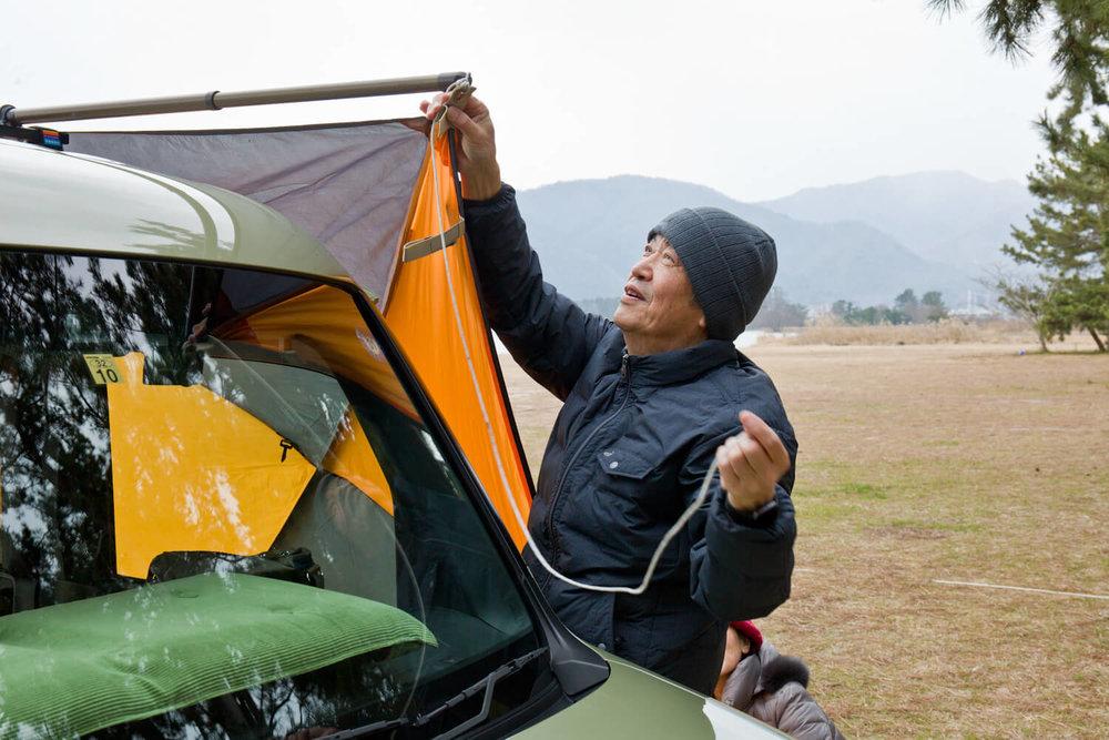 ルーフに設置した物干し竿にタープを取り付ける男性